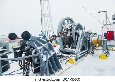 The mooring deck of a cargo ship with anchor winches, an anchor chain on winches, bollards and haws with mooring ropes, frozen and covered in snow. Snow on the mooring deck of a cargo ship.