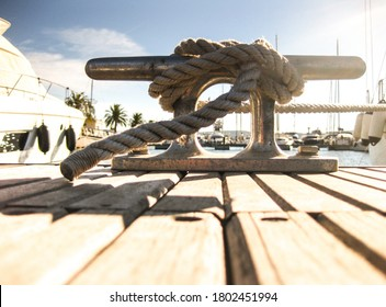 Mooring line tied with a cleat hitch to a nautical horn cleat on a dock.