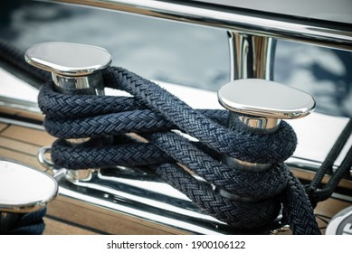 Mooring lines wrapped around a big stainless steel cleat of a superyacht at dock - Shutterstock ID 1900106122