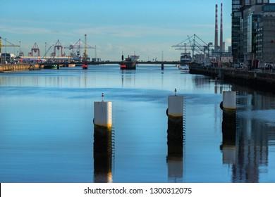 Mooring posts in the harbor. Buildings, cranes, ships, blue sky. Dublin, Ireland, Europe.