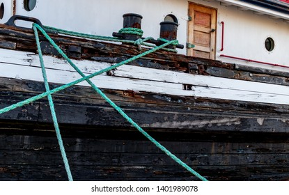 Mooring rope attached to a boat with a door and peeling paint
