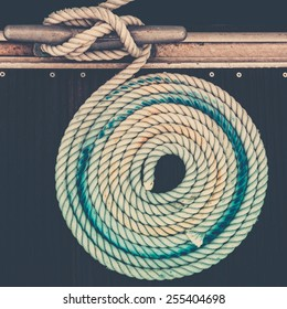 Mooring rope with a knotted end tied around a cleat on a pier