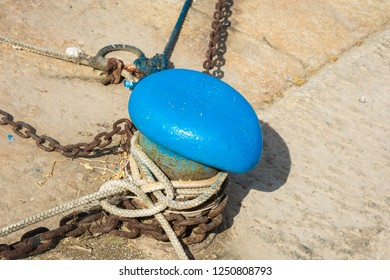 mooring rope of a little ship in the port. Mooring rope and bollard on sea water