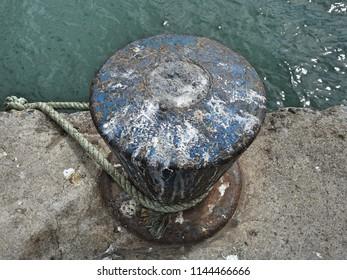Mooring rope tied around a mooring post or bollard in Skerries harbour, Dublin, Ireland standing over sun dappled sea
