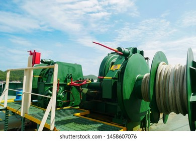 Mooring winch, Mooring windlass for anchor chain on board, forward deck with rope in drum of cargo ship on blue sky background.