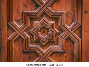 Moorish arab islam decoration on a wooden door in Granada, Spain, near the Alhambra