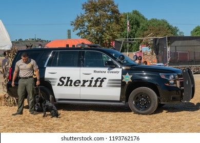 Moorpark, California, USA - September 30, 2018: closeup of black and white Sheriff K9 police car of Ventura County with officer and dog. Blue sky and yellow straw.