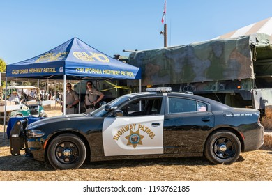 Moorpark, California, USA - September 30, 2018: closeup white and black California Highway Patrol car with two officers in back during harvest fair under blue sky and on yellow straw.
