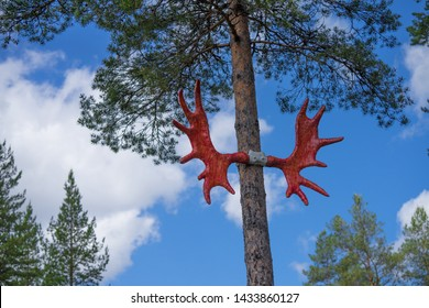 Moose (or elk) antlers attached to the tall pine trees in Norway. Antlers are painted red and they lead the way to the Storelgen (The Big Elk) on road E3 in  Norway.