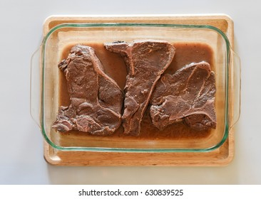 Moose Steaks marinating in glass dish on cutting board
