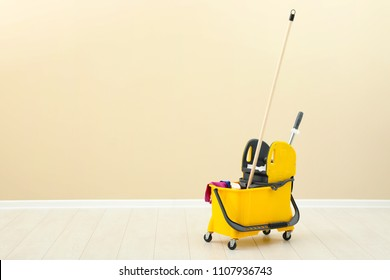 Mop bucket with cleaning supplies on floor near light wall