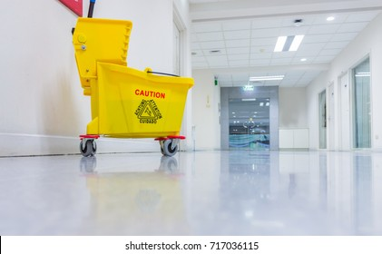 Mop bucket and wringer with caution sign on black floor in walkway office building.