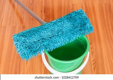Mop and green bucket on wooden floor