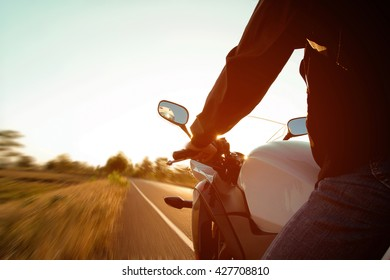Moped drivers on road at sunset - Travel by motorcycle Concept
