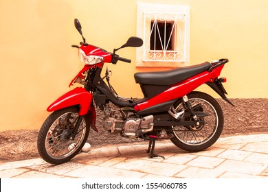 Moped, red scooter stands parked against the wall of the house