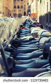 Mopeds scooters parked in a row - blurred background.