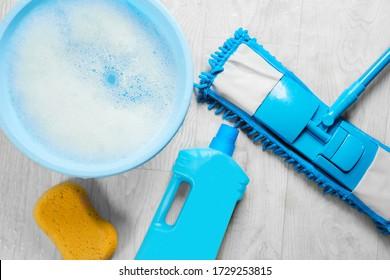 Mopping, blue wet microfiber mop with detergent. Cleaning disinfection kit on a white floor isolated. Housekeeping concept