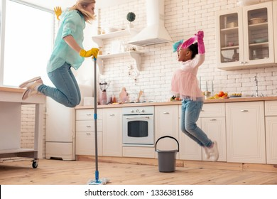 Mopping and jumping. Mother and daughter jumping while mopping the floor and listening music