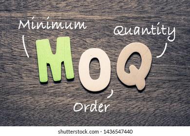 MOQ wooden alphabets on wood background with text acronym (Minimum Order Quantity)