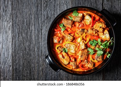 Moqueca baiana - brazilian fish stew of white fish with sweet pepper, lime, chopped tomatoes, coconut milk, served in a black dish with fresh coriander on a dark wooden table, top view, copy space