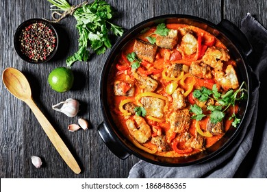 Moqueca baiana - brazilian fish stew of white fish with sweet pepper, lime juice, chopped tomatoes, coconut milk, served on a black dish with cilantro on a dark wooden background, top view