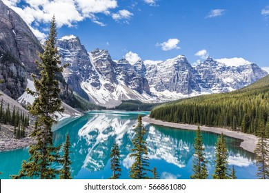 Moraine lake in Banff National Park, Canadian Rockies, Canada. Sunny summer day with amazing blue sky. Majestic mountains in the background. Clear turquoise blue water.