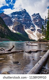 Moraine lake with tree branches in the front. Mountains in the background.