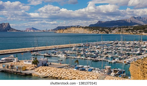Moraira, Spain - April 10th 2019: A view over the harbour in the coastal town of Moraira in Spain.  The town of Calpe is in the distance.
