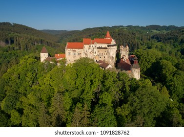 Moravian castle Pernstejn, standing on a hill above deep forests of the Bohemian-Moravian Highlands against blue sky. Aerial photography. Ancient royal castle in Czech landscape, czech travel place.