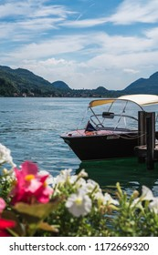 MORCOTE, LAKE LUGANO, SWITZERLAND - JUNE 15, 2018: Beautiful wooden boat on serene Lugano lake surrounded by flowers blossoms and clear blue sky in Morcote, Switzerland.