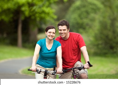 A more closer shot of a young couple, hugging and smiling at the camera and sitting on their bicycles.- horizontally framed
