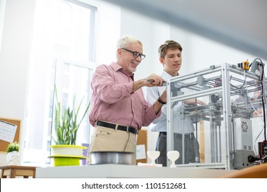 More effective together. Pleasant senior man measuring a 3D model with caliper while his intern putting the parameters into text document on tablet