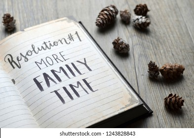 MORE FAMILY TIME Resolution No. 1 written in notebook with pine cones on wooden background