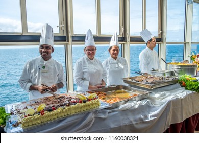 More og Romsdal, Norway - august 6, 2018: Group of chefs serving at a buffet in the pool area of a cruise ship en route through the Norwegian Fjords