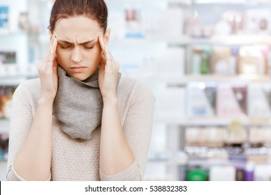 More than just a headache. Closeup portrait of a young female customer rubbing her temples while buying medicine at the drugstore