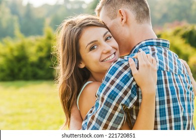 More than love. Beautiful young woman bonding to her boyfriend and smiling at camera while both standing outdoors