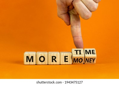 More time or money. Businessman turns wooden cubes and changes words 'more money' to 'more time' or vice versa. Beautiful orange background, copy space. Business, more time or money concept. - Shutterstock ID 1943475127