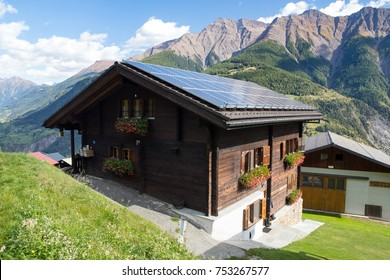 MOREL, SWITZERLAND - SEPT. 24, 2017: Traditional swiss chalet with flowers, in a mountainous landscape with solar energy panels on the roof.