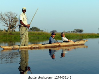 Moremi, Botswana - August, 24, 2013: Tourists are canoeing with a safari guide on the Okavango delta
