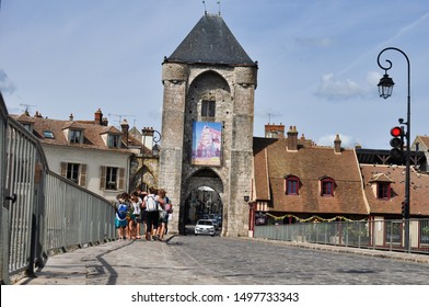 Moret sur Loing , France : August 21, 2019 : The bridge going to the city centre with an old tower and children crossing it on the foreground.