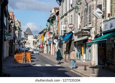 MORET-SUR-LOING, FRANCE - OCTOBER 1, 2018: Pedestrians crossing the Rue Grande (Grand Street). The Rue Grande with its bars and shops and the Paris Gate is a major street of the town Moret-sur-Loing.