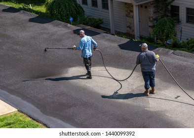 Morgantown, West Virginia - 3 June 2019: Workers applying blacktop sealer to asphalt street using a spray