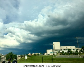 Morgantown, West Virginia, USA - July 3, 2018: Ominous thunderstorm clouds loom over West Virginia University's Creative Arts Center (foreground) on its Evansdale Campus on a hot summer afternoon.