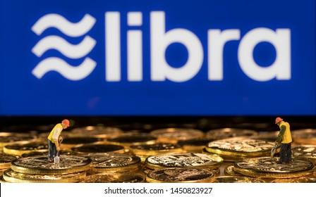 Morgantown, WV - 14 July 2019: Golden cybercurrency coins stacked in front of display showing Libra symbol with miners as concept for Facebook Libra blockchain currency