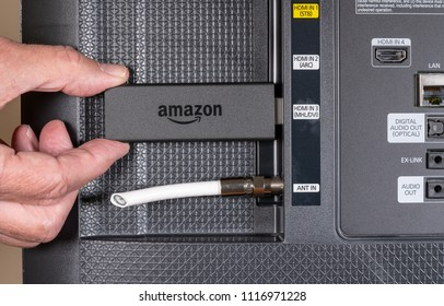 MORGANTOWN, WV - 20 JUNE 2018: Senior hand inserting Amazon Fire streaming stick after cutting cable connection