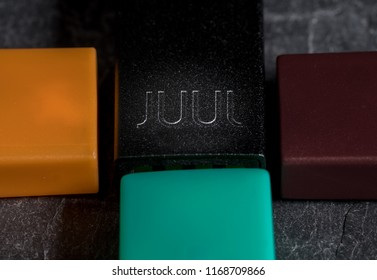 MORGANTOWN, WV - 24 AUGUST 2018: Juul e-cigarette or nicotine dispenser on top of JUULpods on slate