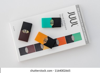 MORGANTOWN, WV - 25 AUGUST 2018: Juul e-cigarette or nicotine vapor dispenser box on and JUULpods on white background