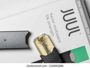 MORGANTOWN, WV - 25 AUGUST 2018: Juul e-cigarette or nicotine vapor dispenser box and JUULpod on white background