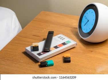 MORGANTOWN, WV - 25 AUGUST 2018: Juul e-cigarette or nicotine vapor dispenser box on bedside table with alarm clock