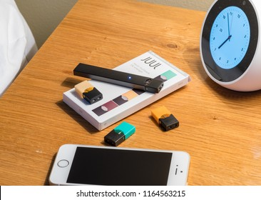 MORGANTOWN, WV - 25 AUGUST 2018: Juul e-cigarette or nicotine vapor dispenser box on bedside table with smartphone